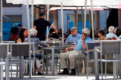 """Personas disfrutan de un soleado día en la terraza de un restaurante en la plaza de la Rinconada, este domingo 21 de junio de 2020, en Valladolid. Después de 98 días de estado de alarma, Castilla y León entraron en una """"nueva normalidad"""" regida por medidas que, aunque más relajadas que las anteriores, tratarán de preservar la prevención y el control de la COVID-19 (EFE/ R. García)"""