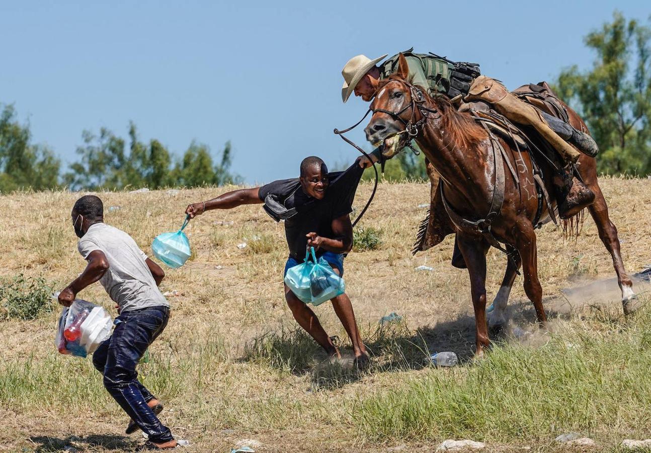 Un agente de la guardia fronteriza de Estados Unidos a caballo intenta evitar que un migrante haitiano ingrese a un campamento a orillas del Río Grande