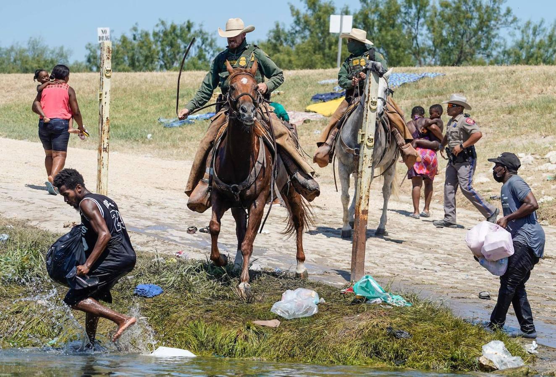 Dos agentes de la guardia fronteriza de EE.UU. usan las riendas de su caballo para evitar que varios migrantes haitianos ingresen al campamento