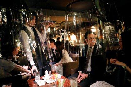 Imagen de pantallas de acrílico similares a una pecera instaladas en un bar como parte de las nuevas medidas de distanciamiento social y prevención de infecciones contra el coronavirus en el distrito de Ginza, en Tokio, Japón (REUTERS/Issei Kato)